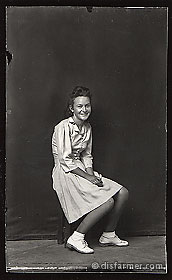Young Woman Smiling, Seated on Stool
